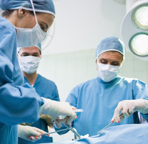 Medical team performing surgery while wearing scrubs