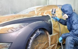 employee in hazmat suit and respirator spray painting a car.