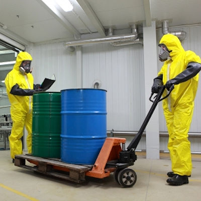 Workers in hazmat suits moving chemicals in barrels.